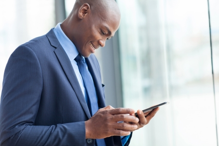 navy blue suit: happy african american entrepreneur using tablet computer Stock Photo