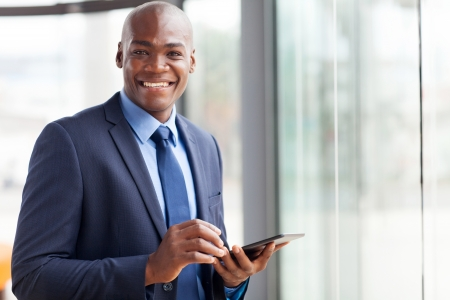 navy blue suit: handsome black businessman using tablet pc Stock Photo