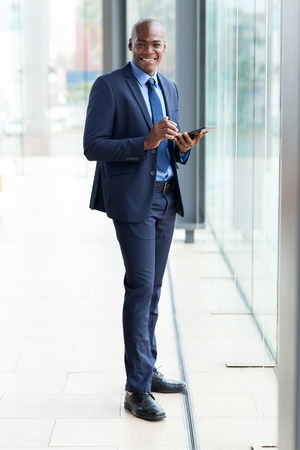 navy blue suit: modern african businessman using tablet computer in office