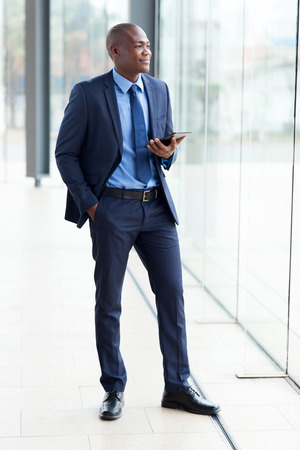 navy blue suit: thoughtful african businessman with tablet computer in office