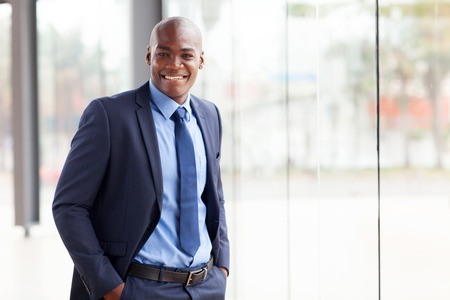 navy blue suit: handsome young african american businessman in office