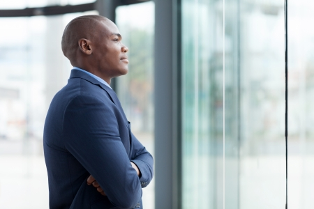 navy blue suit: thoughtful african businessman with arms crossed in office Stock Photo