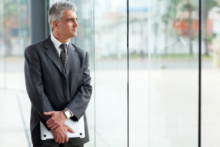 business men: thoughtful mid age businessman looking through office window