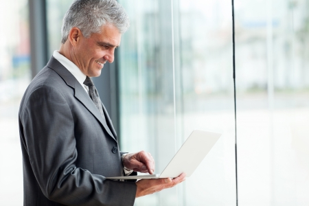 side view of senior businessman working on laptop  Stock Photo