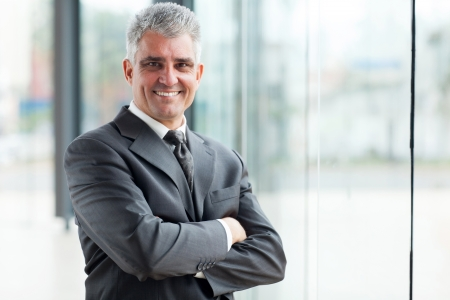 smiling senior businessman with arms crossed photo