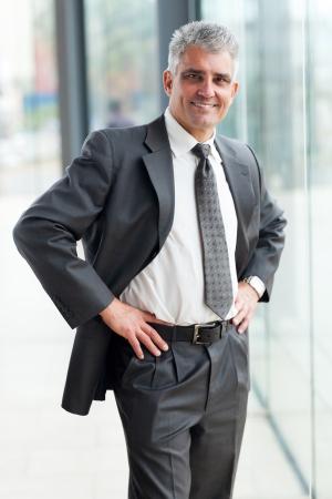 hands on waist: happy senior businessman portrait in office with hands on waist