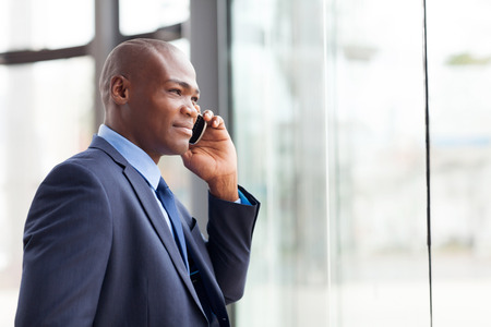 handsome african american businessman talking on mobile phone in modern office photo