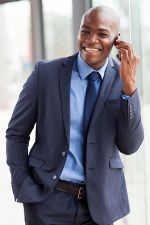 navy blue suit: cheerful african american businessman talking on cell phone