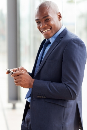 navy blue suit: happy african american businessman reading email on smart phone