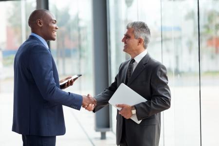 saludo de manos: Alegre dos hombre de negocios apret�n de manos en la sala de conferencias Foto de archivo