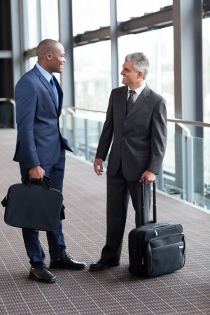 black businessman: two friendly businessmen talking at airport