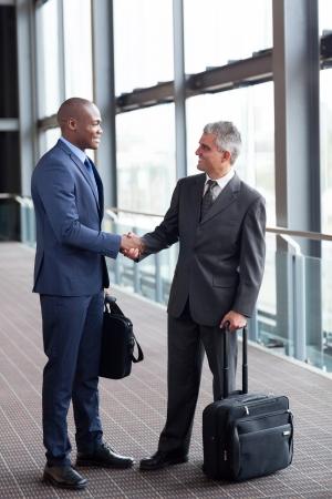 přátelský: šťastné obchodní cestující setkání na letišti
