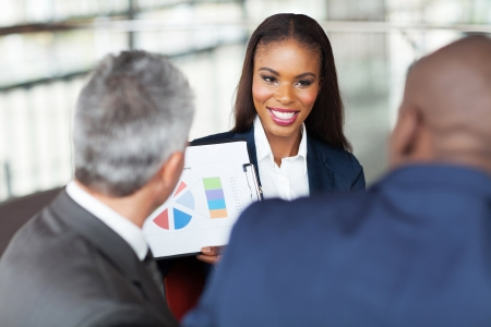 beautiful young african businesswoman explaining graph to business team Stock Photo - 23152744