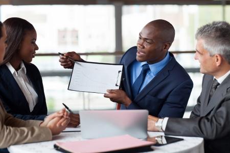 knappe jonge Afrikaanse Amerikaanse zakenman presenteren cijfers op een bijeenkomst met team Stockfoto
