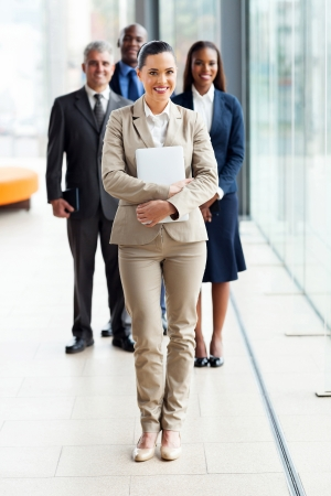 beautiful young businesswoman standing in front of colleagues photo