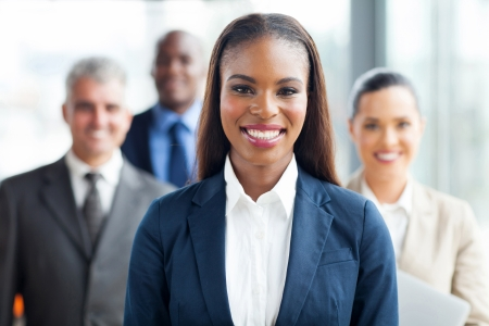 pretty african american businesswoman standing in front of co-workers photo