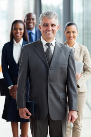 cheerful senior business leader standing in front of his team in office photo
