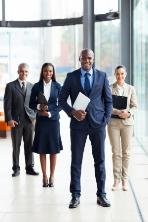 african business man: confident male african business leader and team in office Stock Photo