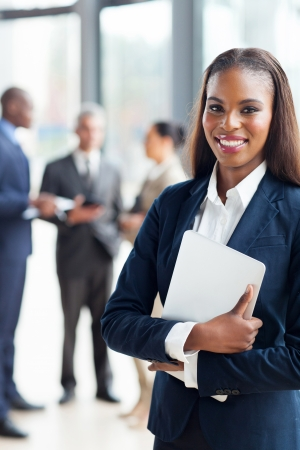 pretty afro american businesswoman holding laptop in office photo