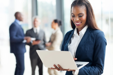 cheerful african american businesswoman using laptop in office photo