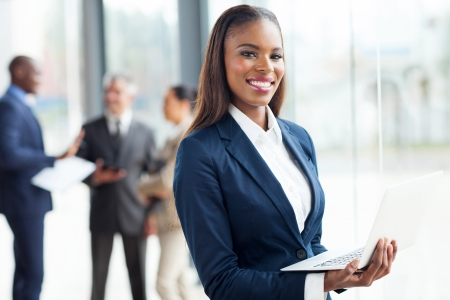 african american woman: smiling african businesswoman with laptop computer