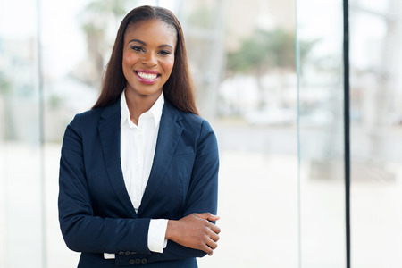 successful business: attractive african american corporate worker standing in office