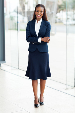 business woman standing: pretty african office worker with arms crossed