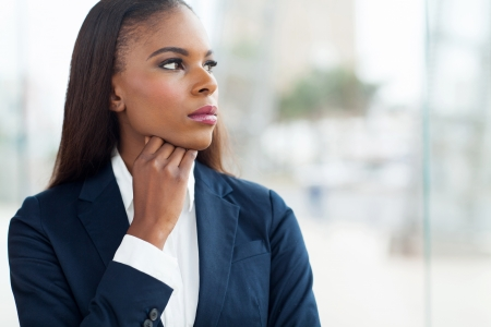 thoughtful african businesswoman looking through window  photo