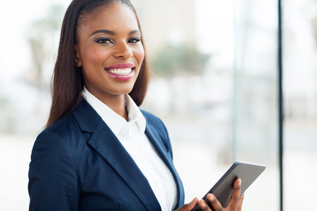 young executives: cheerful black businesswoman with tablet computer in modern office