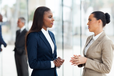 successful female colleagues having conversation in office photo