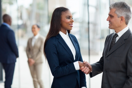friendly senior businessman handshaking with young businesswoman in office Stock Photo