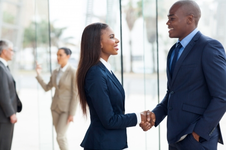 black handshake: professional african business people handshaking in office