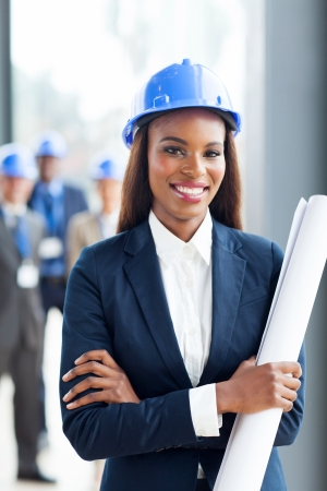 female architect: attractive young african construction manager holding blue print in office