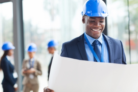 smart african construction businessman reading blue print photo