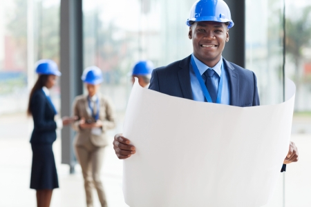 smiling african architect holding blue print in office photo