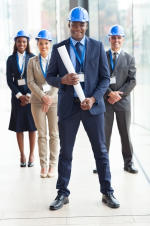 happy african american architect standing in front of colleagues in modern office photo