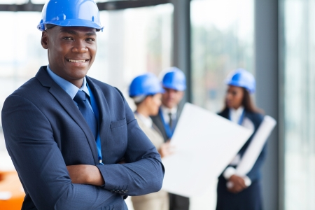 team success: african male construction manager with arms folded