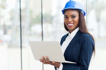 construction helmet: attractive young african architect using laptop in office