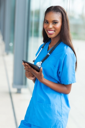 beautiful young african nurse holding tablet computer in office photo