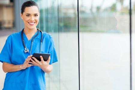 魅力的な女性看護師の病院でタブレット コンピューターを使用して 写真素材