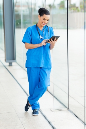 nurse computer: cheerful young medical doctor using tablet pc