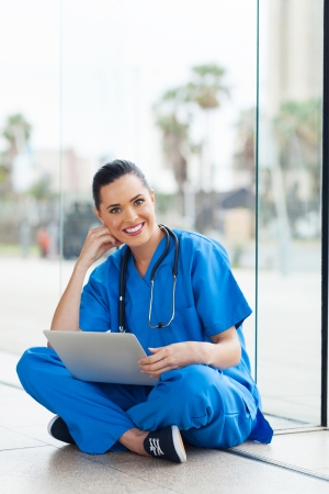 smiling healthcare worker with laptop computer sitting on the floor photo