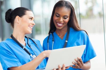 scrub: two pretty nurses using laptop computer