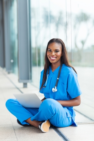 pretty black healthcare worker using laptop at work