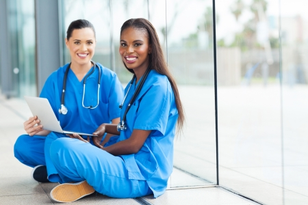 attractive female doctors sitting on the floor using laptop photo