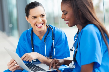 doc: beautiful young female nurses having fun with laptop Stock Photo