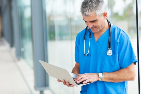 male nurse: modern senior doctor working on a laptop  Stock Photo