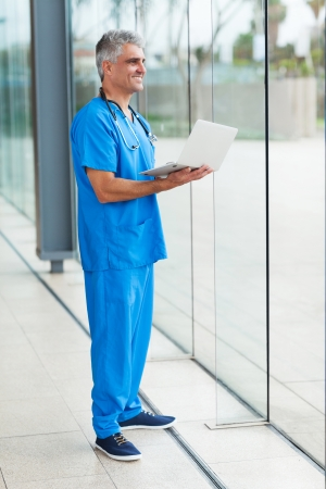middle aged healthcare worker holding laptop computer at hospital photo
