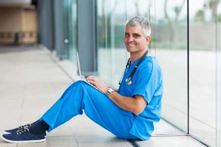 senior medical worker sitting on hospital floor and using laptop computer photo
