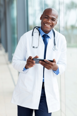 cheerful african american medical doctor using tablet pc photo